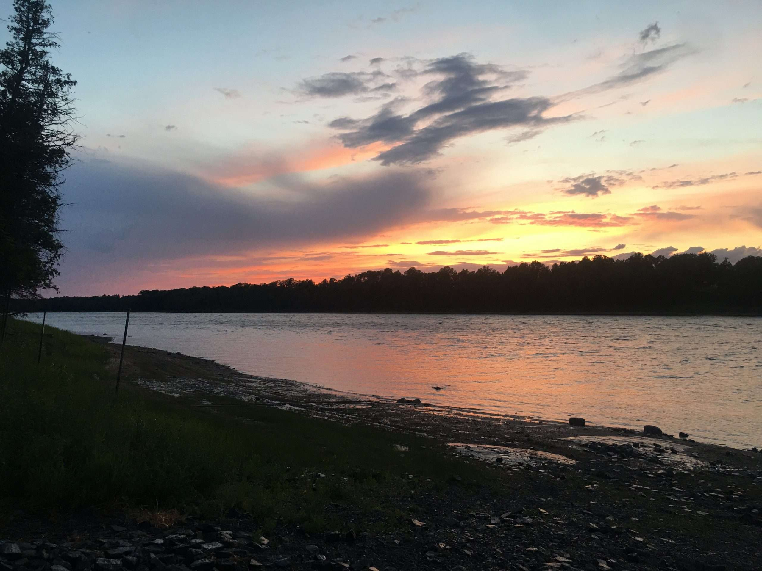 the sun sets across a river