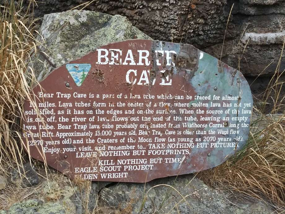 """a well worn sign reads """"Bear Trap Cave"""" and other unreadable texts"""
