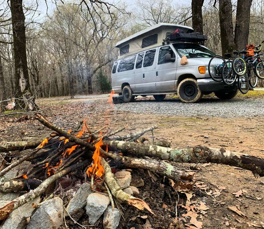 a van camping, with a campfire, in an Arkansas forest