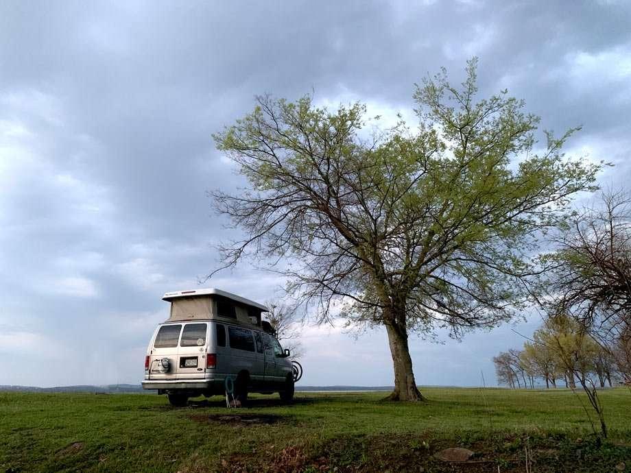 a van camps beneath a heart-shaped tree