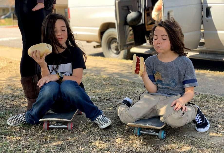 two children sit on skateboards and eat bratwurst