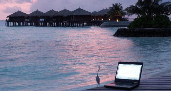 a laptop on a pier near a beach town