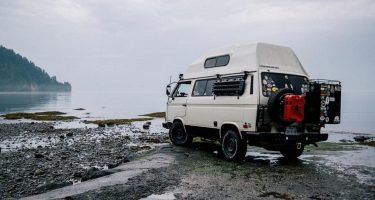 a white vanagon with a high top and a bunch of gear on the back, in a rather kick ass setting if i do say so myself
