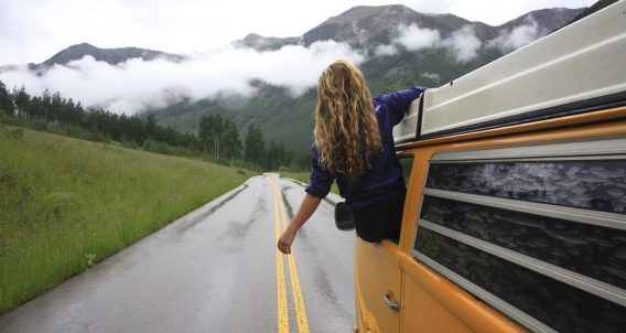 Rachel of Idle Theory Bus hangs from the window of their Volkwagen Bus as they traverse some road