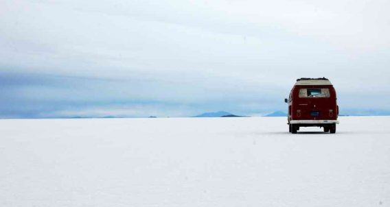a red 1971 Volkswagen Bus parked on an endless desert beach