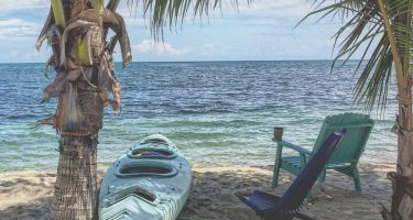 two wooden chairs next to the caribbean sea in placencia, belize