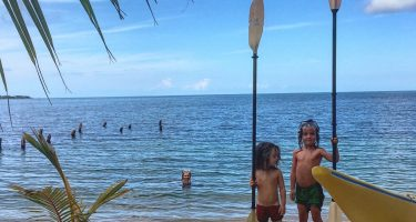 two boys stand with paddles, next to a kayak and the Caribbean sea, their older brother swimming in the pristine waters