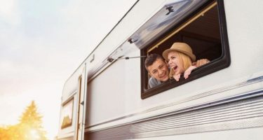 a young couple smiling and laughing out of an RV