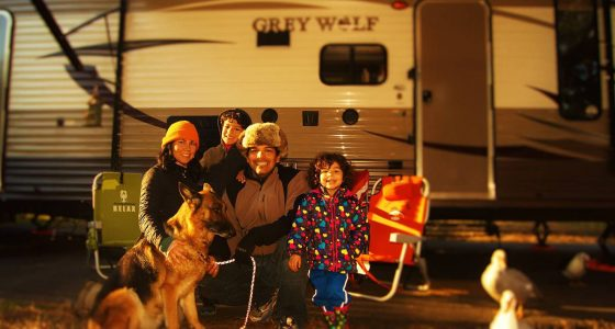 a family of four and their dog sit in camping chairs outside of their Grey Wolf travel trailer