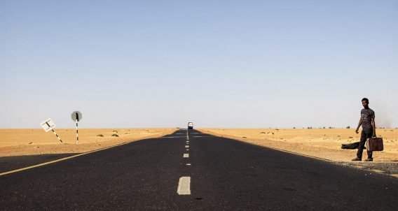 a hitchhiker with a guitar along a long dusty road