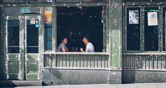 two men sit at a bar
