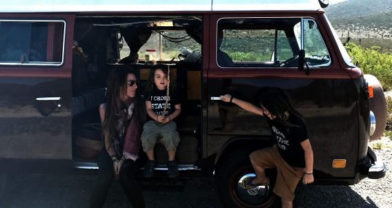 a mama and her ninos hanging around their bus