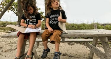 two young boys wearing t-shirts, doing junior ranger books at a state park in florida