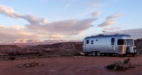 an airstream travel trailer parked in the desert, snowcapped mountains in the distance