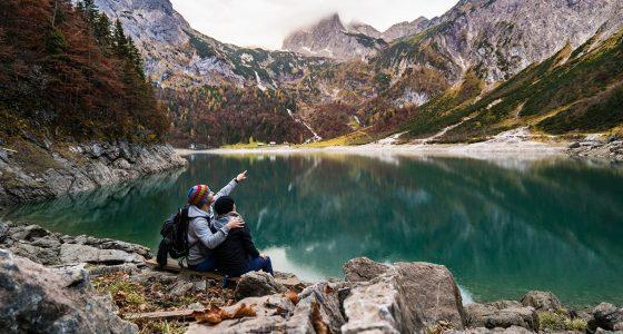 a couple sitting near an alpine lake enjoying their travels