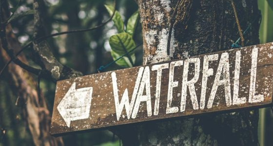 a sign pointing to a waterfall