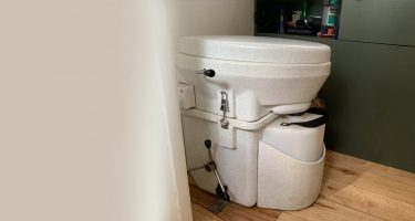 a composting toilet in the bathroom of a vintage airstream