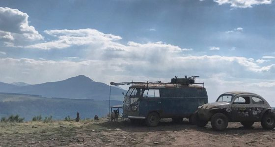 a classic VW bus and Superbeetle parked, without any hookups, atop a cliff, camping in the wild, AKA boondocking