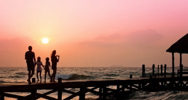 silhouetted family walking on a peer at sunset