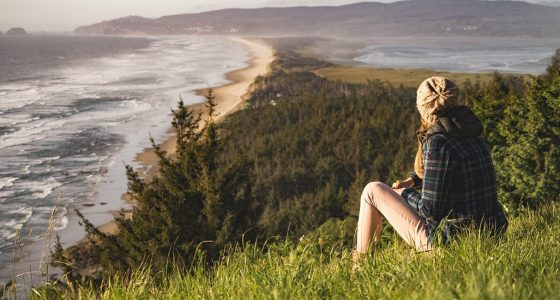 a young woman sits in a field overlooking the ocean