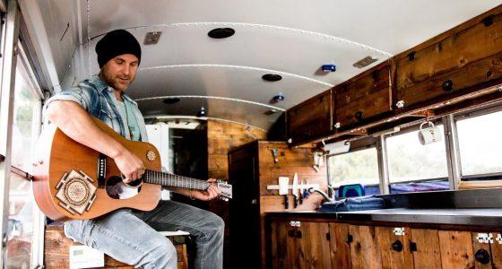 Prem Yogi plays guitar in his converted school bus