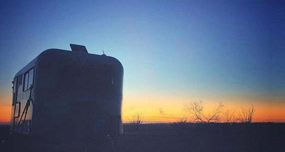 a travel trailer, sunset, parked in the desert