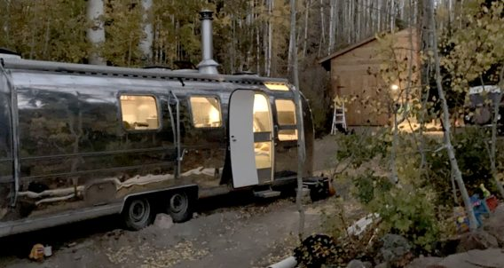 an airstream, cabin and VW Bus in the forest