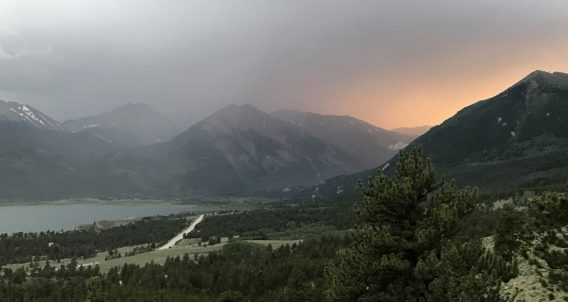 thunderous weather above a lake and winding road through the rocky mountains of coloradothunderous weather above a lake and winding road through the rocky mountains of colorado