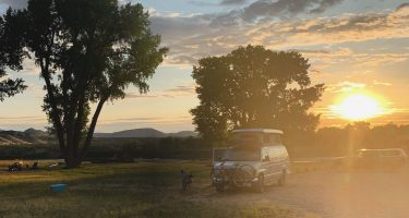A van parked in the setting sun of Dinosaur National Monument