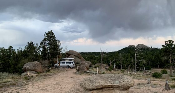 a van camping, alone, amongst the large boulders and trees of the Pole Mountain area of Medicine Bow National Forest in Wyoming