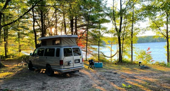 A van camping within the beginning throws of autumn lakeside in michigan