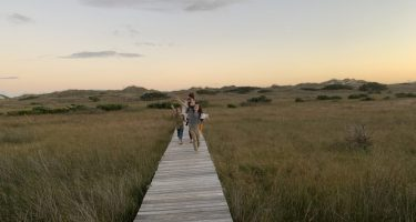 A family walks along a boardwalk near the ocean in Cape Hatteras National Seashore
