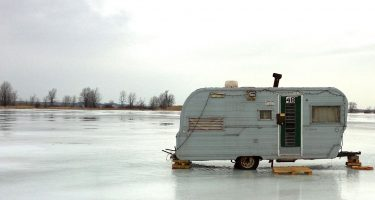 a vintage travel trailer parked on ice in the winter