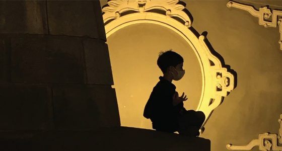 a boy in a mask practices meditation in a golden room