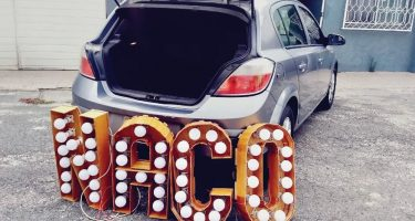 """A sign reads """"Naco"""" in neon lights leaned against a car"""