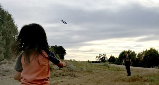 two brothers toss a frisbee back and forth at a free camping spot in Colorado