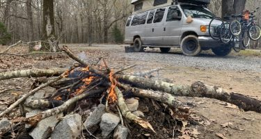 A silver Ford campervan parked near a campfire in Arkansas