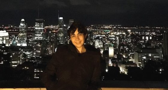 a woman stands in front of a city of lights at night