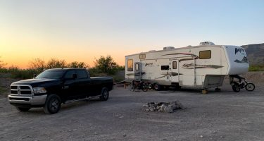 a pickup truck, fifth wheel and motorcycles camping in the desert