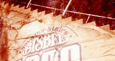 a staircase climbs above a painted sign alongside reading save our stairs, bisbee 1000