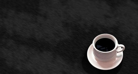 a cup of black coffee in a simple white mug, with saucer