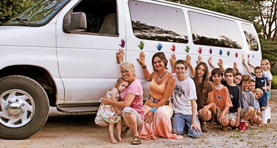Two mothers and eleven children lean against a white van with tinted windows, ranging in ages, with handprints stuck to the side of it