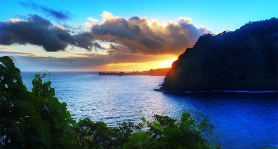 view from the Road to Hana, silhouetted cliffsides tower over crystal blue waters, the sun sets golden beneath clouds in a bright blue sky