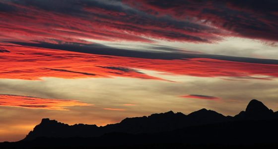 a brilliant sky, red vivid cast deep on the bottoms of passing clouds as the sun has set behind the West Texas mountains