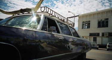 a station wagon with a bull's horns mounted to the roof, a painting mimicking the reflection of marfa, tx.