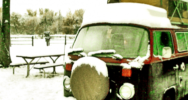 a 1970s Volkswagen Bus, dollops of snow on its icicle clad roof and spare front tire