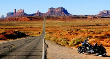 the auburn desert stretches out, mesas poised against a pristinely clear sky, a Harley Davidson parked alongside the road