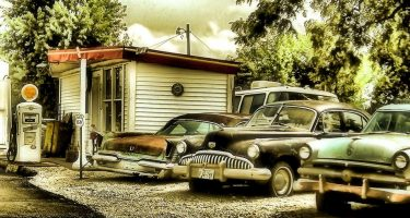 vintage cars outside of a gas station in some beautiful wooded locale