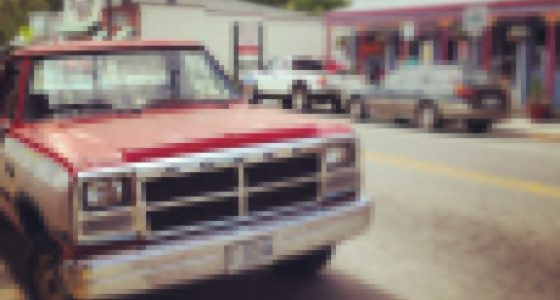 an old red dodge pickup on a lazy main street