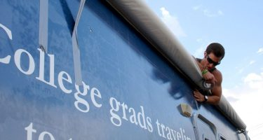 a college student atop an rv that reads College grads traveling...